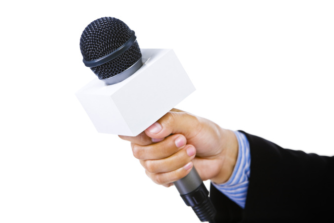 Side view of and hand using suit holding a microphone aiming to the empty space on the left. Focus mainly on the microphone.