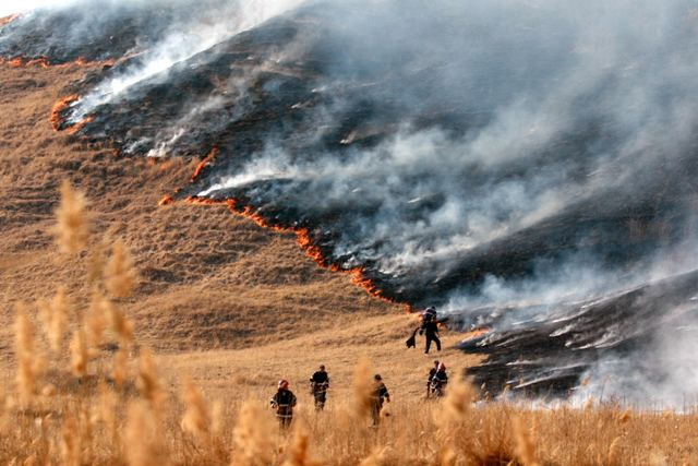 """Sapte pompieri incearca sa stinga focul izbucnit in apropierea rezervatiei naturale """"Vulcanii Noroiosi"""", la Buzau, sambata, 17 martie 2007. Cel mai probabil, incendiul a fost provocat de localnicii care au demarat curatenia de primavara, au strans resturile vegetale de pe camp, le-au incendiat si nu au supravegheat focul. CIPRIAN STERIAN / MEDIAFAX FOTO"""
